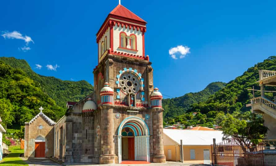 The colourful Soufrière church in Dominica, with green hillside and blue sky behind