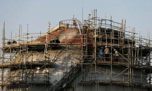 Workers are seen at the damaged site of Saudi Aramco oil facility in Abqaiq, Saudi Arabia