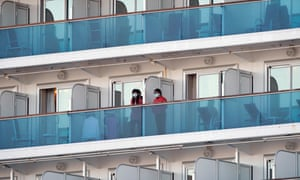Passengers of the Diamond Princess cruise ship stand on their cabins' balconies.