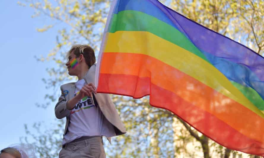 A supporter waves a rainbow flag at a marriage equality rally.