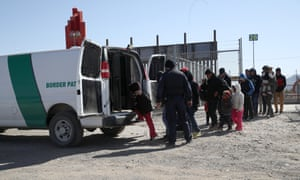 US border patrol agent loads detained migrants into a van at the US-Mexico border on 31 March in El Paso, Texas.