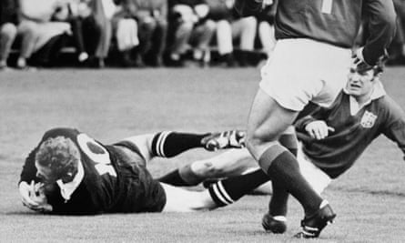 Wayne Cottrell (left) of the All Blacks dives past Mike Gibson to score the Kiwis' first try in the fourth Test in Auckland.