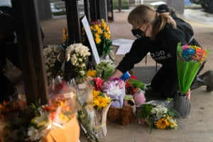 Shelby Swan adjusts flowers and signs outside Young's Asian Massage where four people were shot and killed on 17 March 2021 in Acworth, Georgia.
