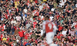 Arsenal fans shield their eyes as Alexandre Lacazette runs past.