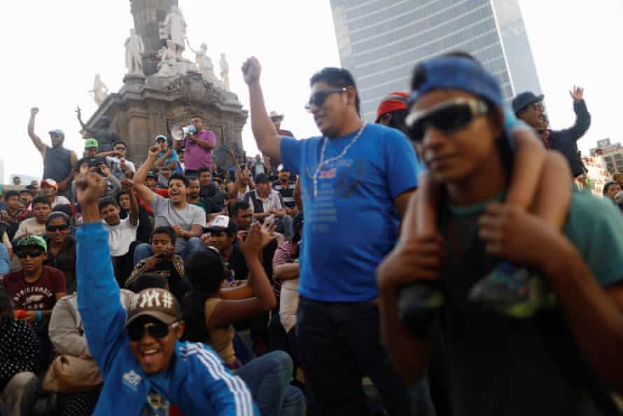 Central American migrants, moving in a caravan through Mexico, gesture in a demonstration at Angel de la Independencia monument in Mexico City, 12 April