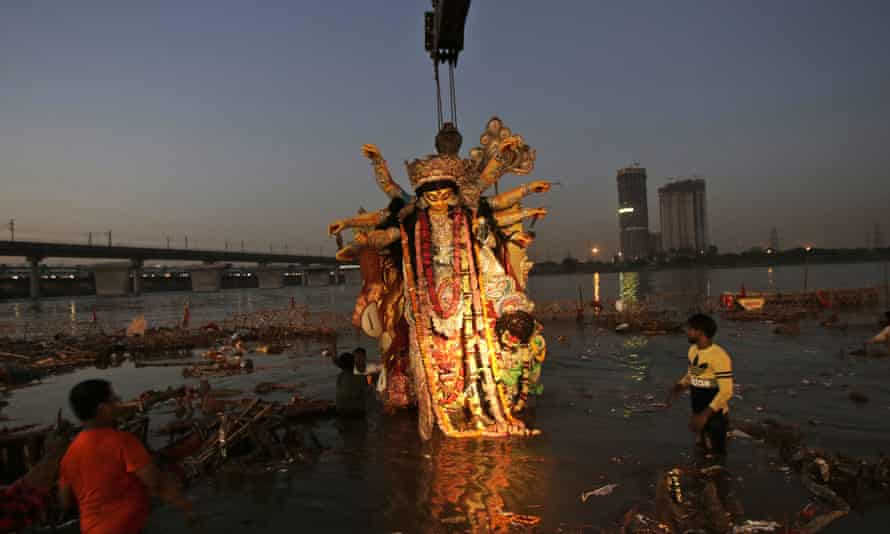 A giant idol of Hindu goddess Durga is immersed in the Yamuna river.