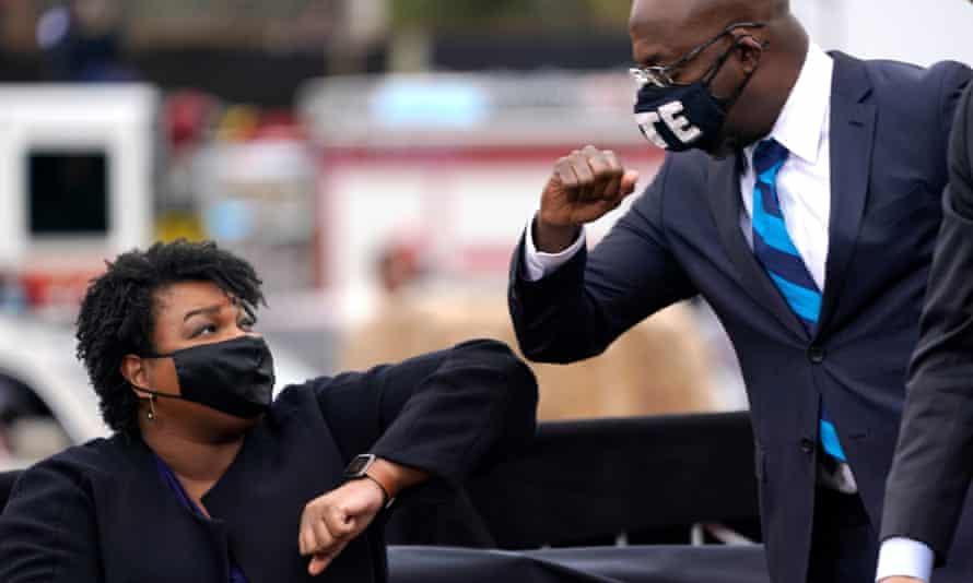 Le candidat démocrate au Sénat Raphael Warnock se cogne les coudes avec Stacey Abrams lors d'un rassemblement avec Joe Biden à Atlanta.
