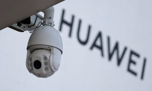 A surveillance camera is seen next to a sign of Huawei.