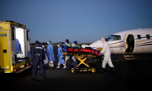 Medical staff move a patient from a plane during a Covid transfer at Vannes Airport.