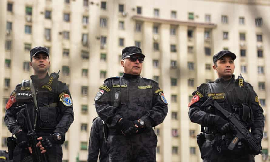 Three armed special forces police stand guard on Tahrir Square, Cairo
