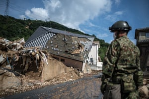 A soldier guards a road next to wrecked houses