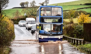 A bus drives through flood water on the main A396 between Tiverton and Exeter, near Upexe