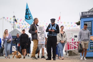 An Extinction Rebellion activist speaks with a police officer in Falmouth