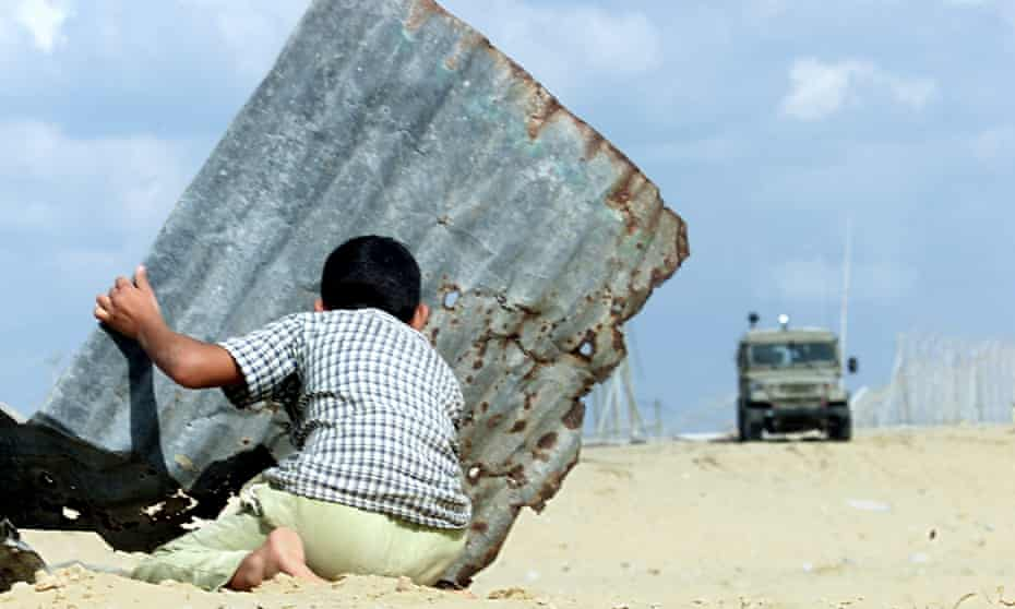 A Palestinian child kneels behind a sheet of corrugated iron as they look at an armoured vehicle