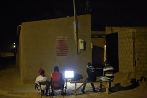 Young men gather around a TV to watch the big game