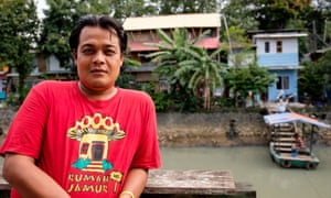 Gugun Muhammad with his home, Kampung Tongkol, in the background.