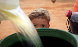 A young Brazilian boy watches as his mother collects water in a barrel.