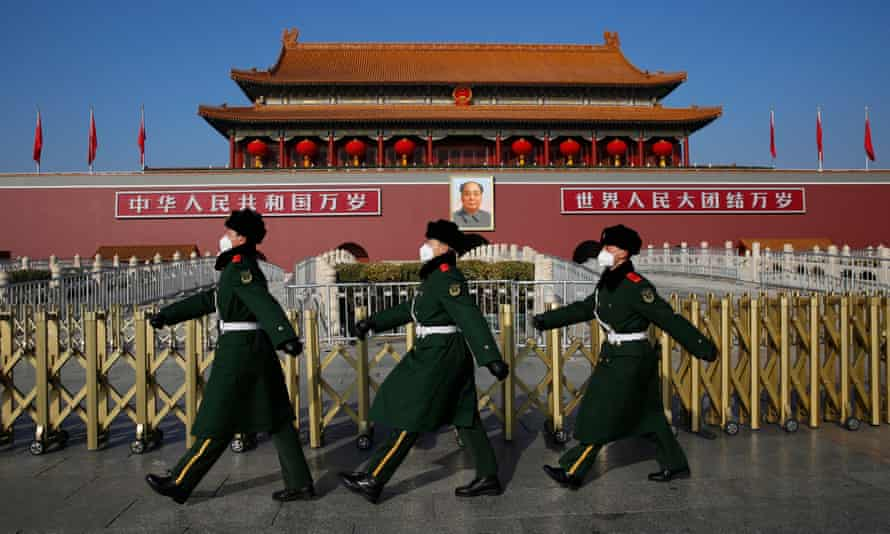 Chinese paramilitary police officers wear masks as they patrol at Tiananmen Square in Beijing, China