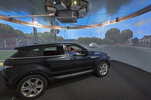 The car sits in a 360-degree cylindrical screen projecting a high-definition, digitally rendered route.