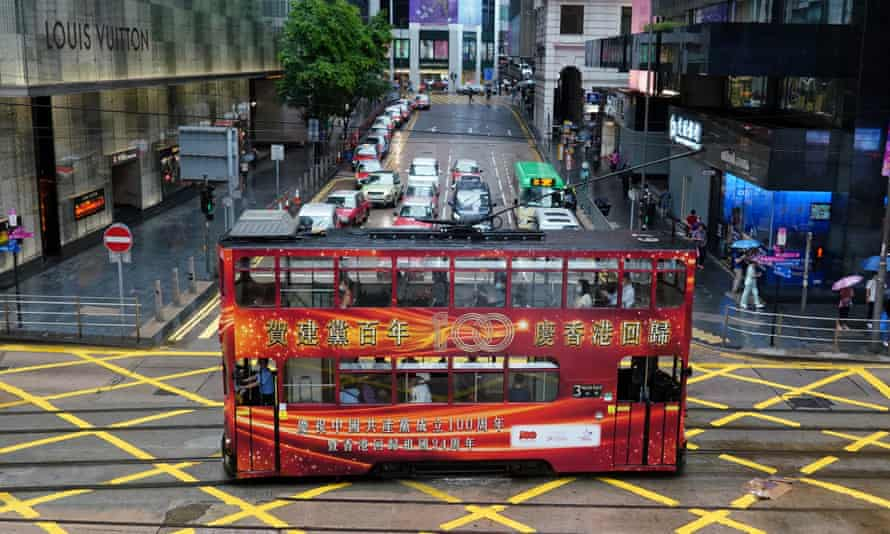 A tram with a slogan celebrating the 100th anniversary of the founding of the Chinese Communist Party and the 24th anniversary of Hong Kong's return to China drives along the street in Hong Kong