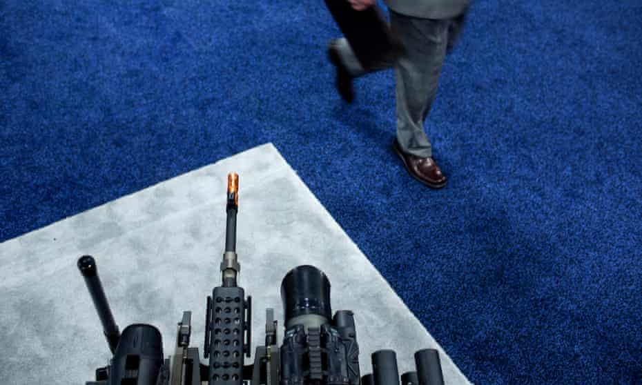 A man walks past an armed robotic system at a trade fair.