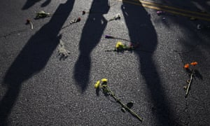 Flowers lie on the street as marchers pass by
