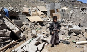 A young Yemeni stands over the rubble of a destroyed house targeted by an alleged Saudi-led airstrike.