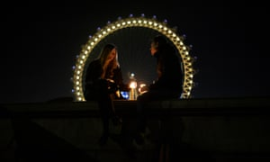 A couple sit on a wall opposite the London Eye with candles.