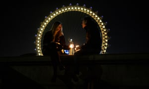 A couple sit on a wall opposite the London Eye with candles on March 23, 2021 in London, England