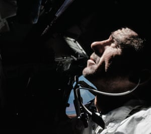 walter cunningham looks out of the command module during Apollo 7's 11-day orbit of earth