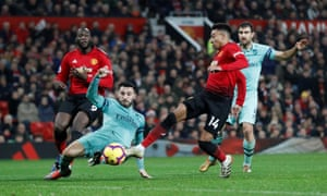 Manchester United's Jesse Lingard nips in to score the second.