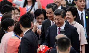 China's President Xi Jinping (2nd R) is greeted by well-wishers upon his arrival at Hong Kong's international airport on June 29