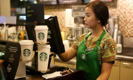 A worker in green apron and batik shirt operates a till in a Starbucks coffee shop in Jakarta, Indonesia