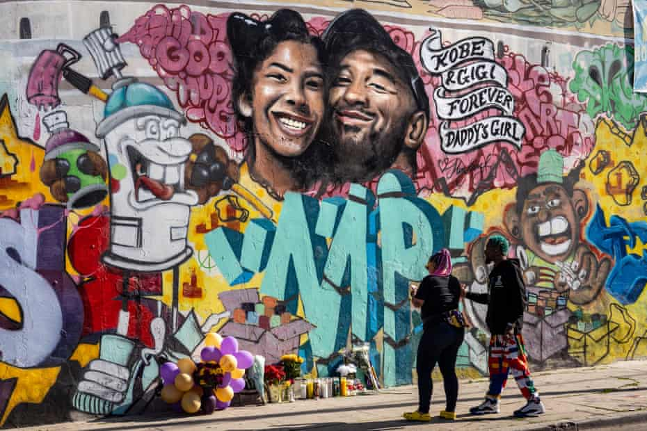 People gather in front of a mural in honor Bryant and his daughter Gianna.