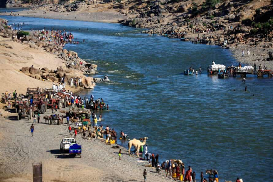 Ethiopian refugees who fled the fighting in the Tigray region gather on the banks of a border river with Sudan on 22 November.