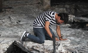 An Iraqi man cries inside a building destroyed by a suicide bombing in Baghdad at the weekend.