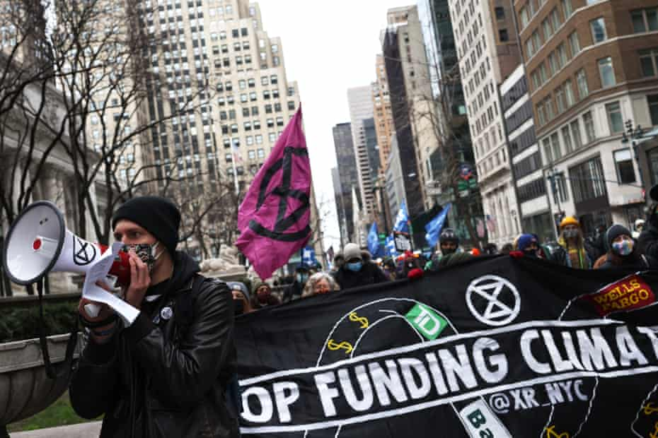 Demonstrators march in New York City on 2 April in solidarity with the #StopTheMoneyPipeline coalition.