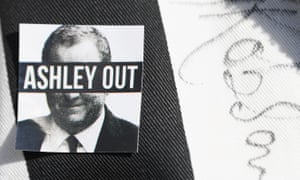 A badge saying Ashley Out on a Newcastle United fan's shirt.