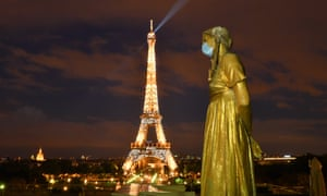 """A Golden Statue at the Trocadero square wears a protective mask near the Eiffel tower with the message """"Merci"""" (thank you) to health workers on 3 May 2020 in Paris, France."""
