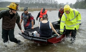 Rescue workers from Township No. 7 Fire Department and volunteers from the Civilian Crisis Response Team use a boat to rescue a woman and her dog in James City.
