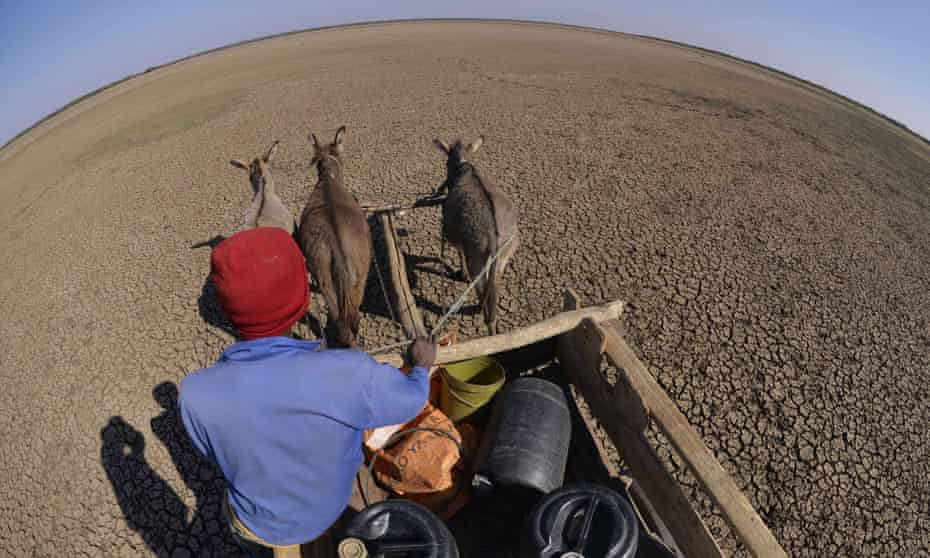 A man crosses the dried Bokaa Dam with a donkey cart on the outskirts of Gaborone, Botswana