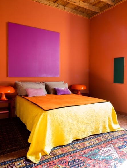 'The colours call out to us': bright orange bedroom with a pair of Gae Aulenti lights.