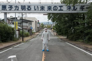 """The photographer Arkadiusz Podniesinski stands on one of the main streets of Futuba, a Fukushima village. The writing above him says: """"Nuclear energy is the energy of a bright future""""."""