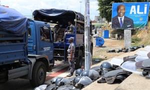Gabonese security forces alongside poster of Ali Bongo