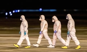 Health officials walk on the tarmac as they prepare for the arrival of five Czech and two Slovak nationals who were evacuated from Wuhan