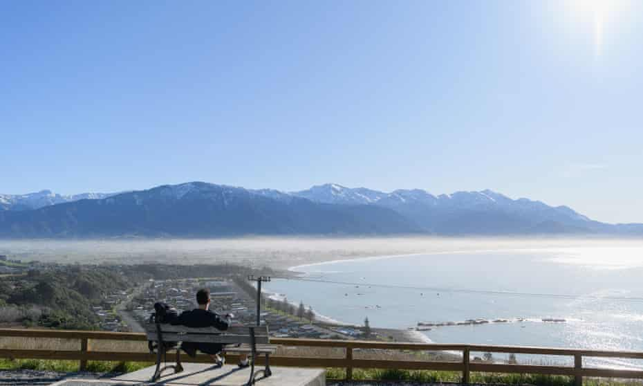 A backpacker looks at the view of Kaikoura and the Kaikoura Ranges in New Zealand