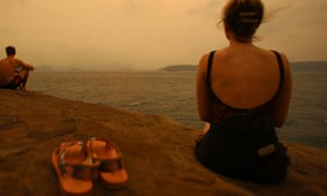 Beachgoers peer though bushfire smoke