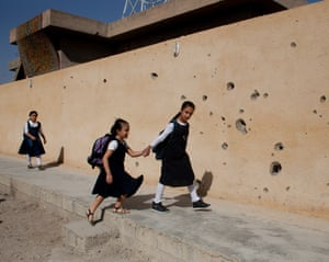 Children make their way to school past war-damaged walls in Jalawla. Photograph: Abbie Trayler-Smith for the Guardian