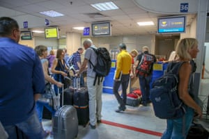 People line up in front of a counter of Thomas Cook at the Heraklion airport on the island of Crete, Greece.