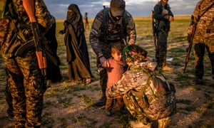 A member of the Kurdish-led SDF holds a toddler during a security check of her and her mother after they left Baghuz.